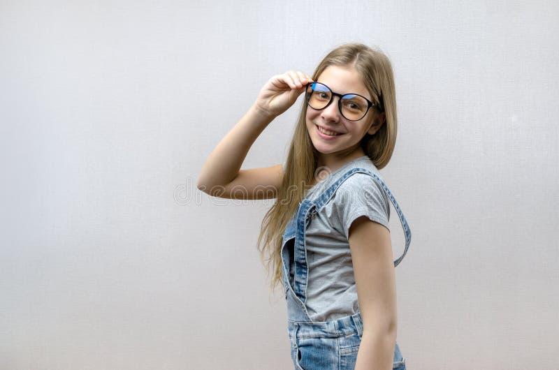 Portret van een glimlachend mooi jong meisje met glazen Slim Kind nerdy royalty-vrije stock afbeelding