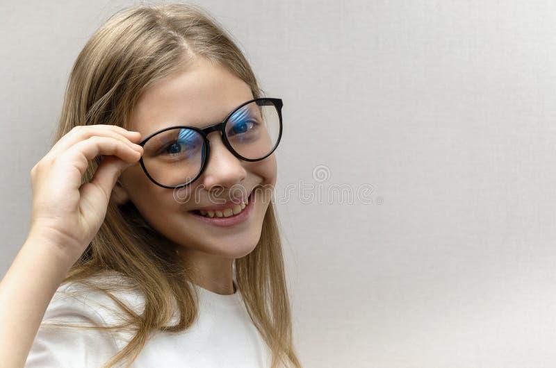 Portret van een glimlachend mooi jong meisje met glazen Slim Kind nerdy royalty-vrije stock afbeeldingen