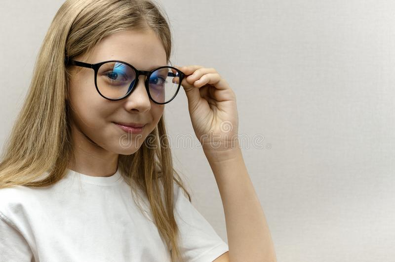 Portret van een glimlachend mooi jong meisje met glazen Slim Kind nerdy stock fotografie