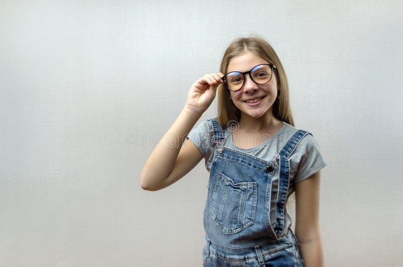 Portret van een glimlachend mooi jong meisje met glazen Slim Kind nerdy stock foto's