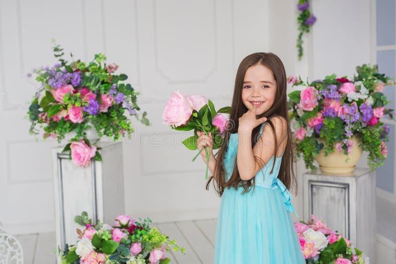 Portret van een glimlachend mooi meisje in een turkooise kleding in een studio met bloemen royalty-vrije stock foto