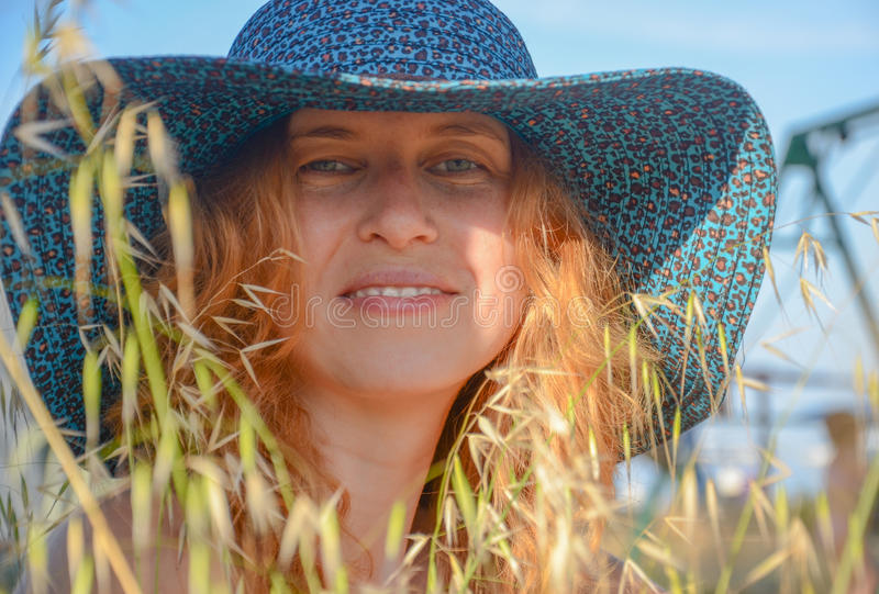 Portret van een glimlachend roodharig meisje in hoed stock afbeelding