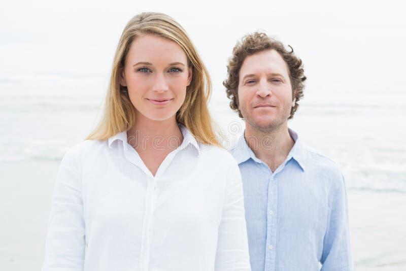 Portret van een glimlachend toevallig paar bij strand stock fotografie