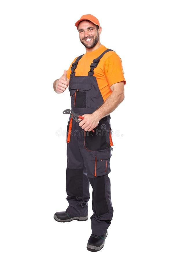 Portret van een glimlachende arbeider in blauwe eenvormige holdingsbuigtang stock foto
