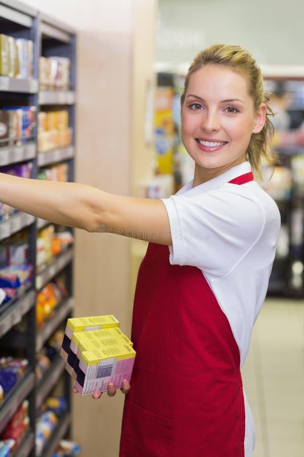 Portret van een glimlachende blondearbeider die een product in plank nemen royalty-vrije stock afbeelding