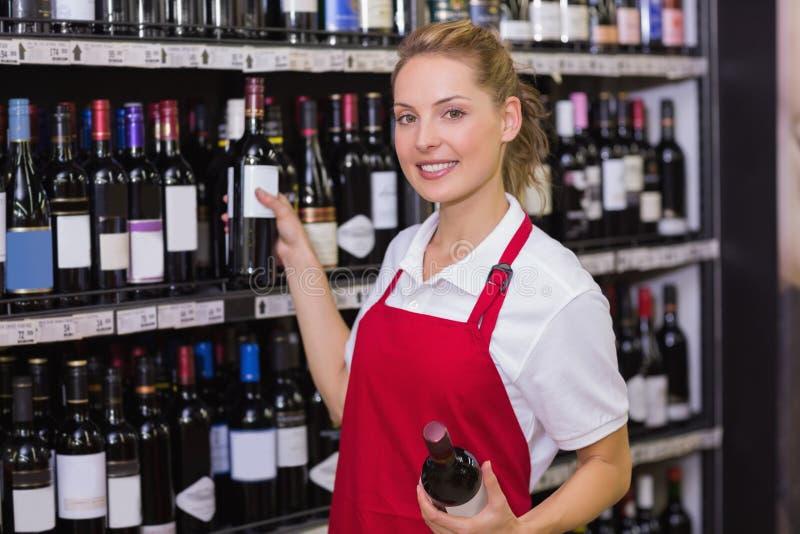 Portret van een glimlachende blondearbeider die een wijnfles nemen stock fotografie