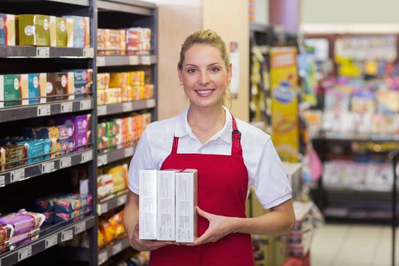 Portret van een glimlachende blondearbeider die producten hebben stock afbeeldingen