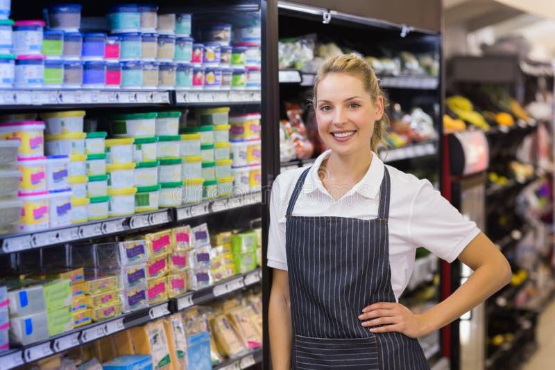 Portret van een glimlachende blondearbeider met hand op heup stock afbeeldingen