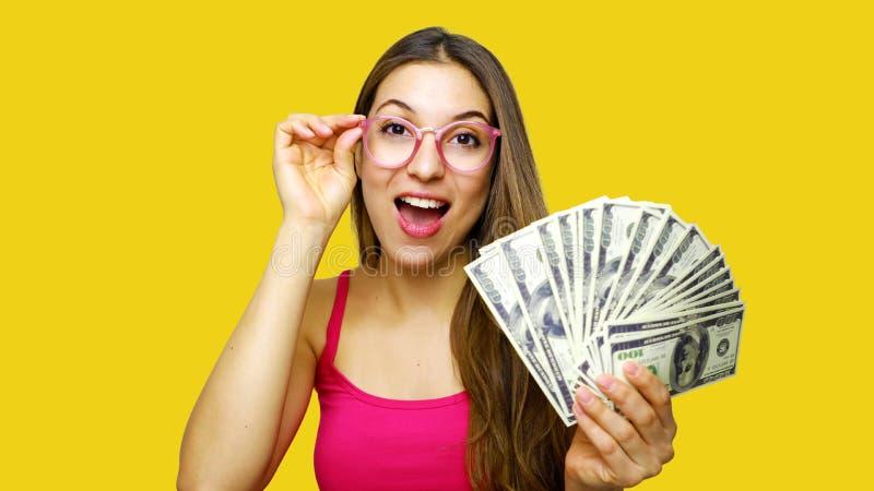 Portret van een glimlachende deskundige vrouw die bos van geldbankbiljetten tonen over gele achtergrond royalty-vrije stock afbeeldingen