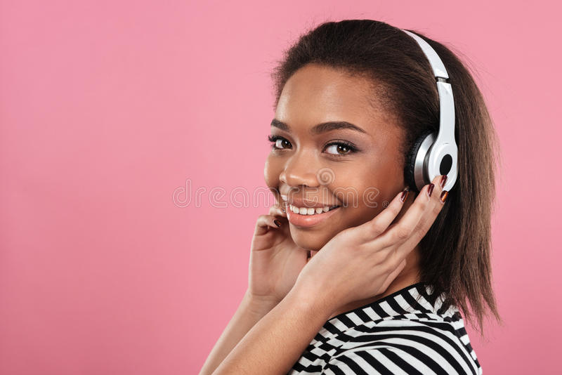 Portret van een glimlachende gelukkige afro Amerikaanse vrouw in hoofdtelefoons stock foto's