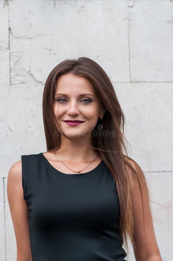 Portret van een Glimlachende Gelukkige Elegante Jonge Vrouw in Zwarte Kleding die zich tegen Blauwe Muurachtergrond bevinden royalty-vrije stock foto's