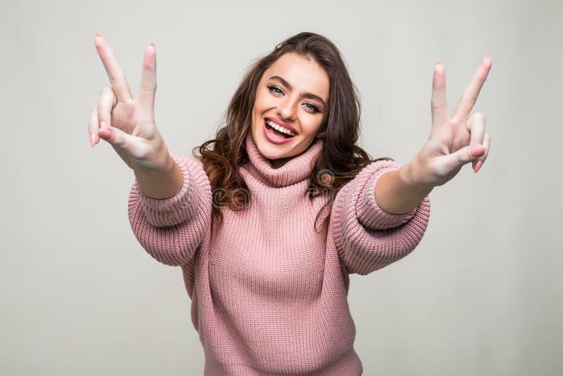 Portret van een glimlachende gelukkige vrouw die overwinningsteken tonen die en camera bekijken op de grijze achtergrond wordt ge royalty-vrije stock afbeelding