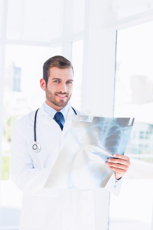 Portret van een glimlachende jonge mannelijke arts die röntgenstraal onderzoeken royalty-vrije stock foto's