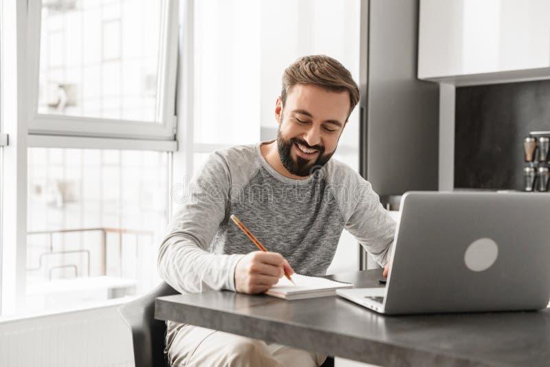 Portret van een glimlachende jonge mens die aan laptop computer werken stock foto