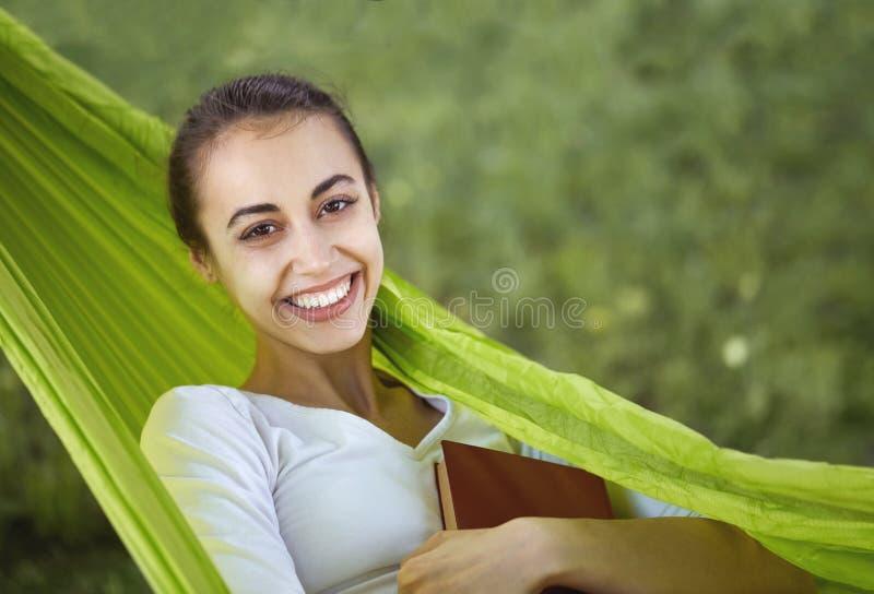 Portret van een glimlachende jonge vrouw die in groene hangmat met boek in park liggen royalty-vrije stock foto's