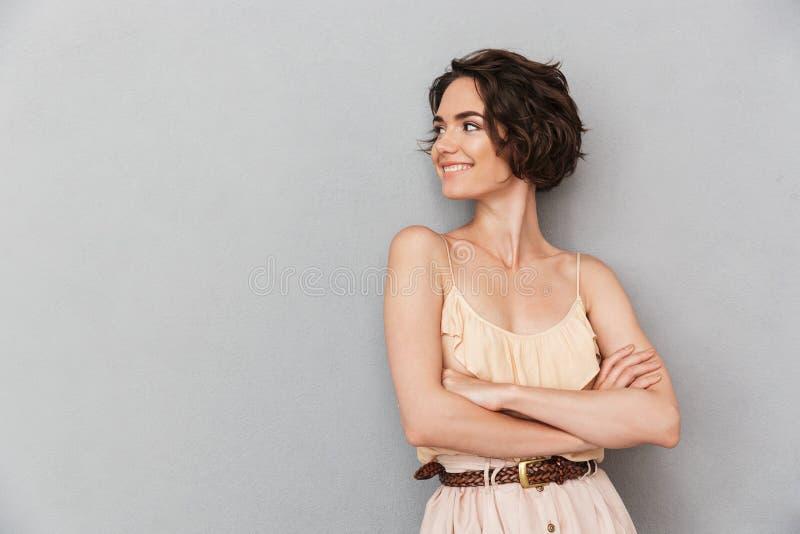 Portret van een glimlachende jonge vrouw die zich met gevouwen wapens bevinden royalty-vrije stock afbeeldingen