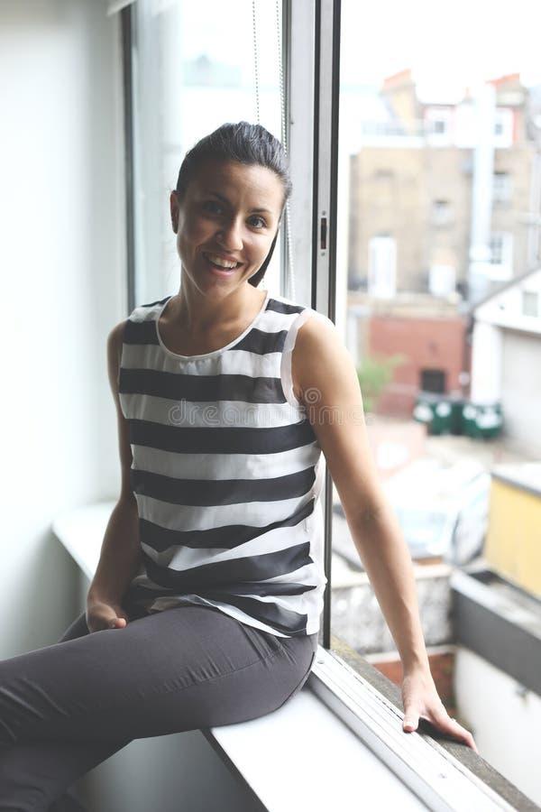 Portret van een glimlachende jonge vrouw door het venster royalty-vrije stock foto's