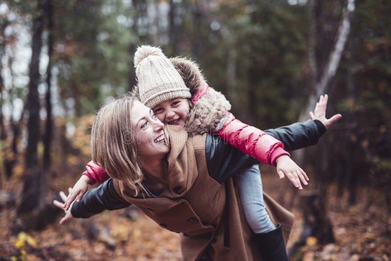 Portret van een glimlachende jonge vrouw met een klein meisje in de herfst stock foto's