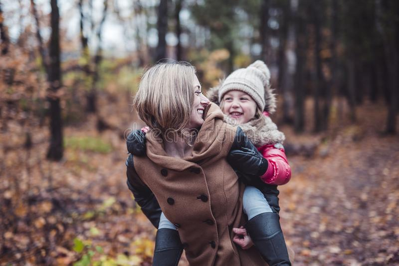Portret van een glimlachende jonge vrouw met een klein meisje in de herfst stock afbeelding