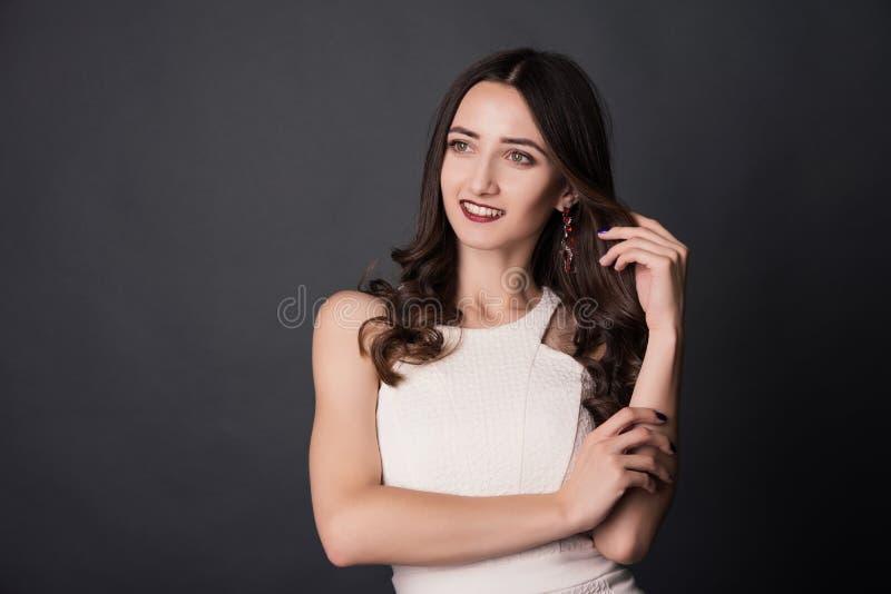 Portret van een glimlachende jonge vrouw wat betreft haar haar over grijze achtergrond stock foto