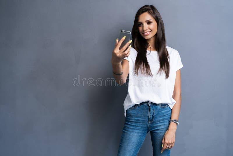Portret van een glimlachende leuke vrouw die selfie foto op smartphone maken die op een grijze achtergrond wordt geïsoleerd stock foto