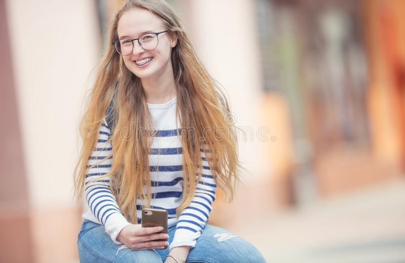 Portret van een glimlachende mooie tiener met tandsteunen Jong schoolmeisje met schooltas en mobiele telefoon stock foto's
