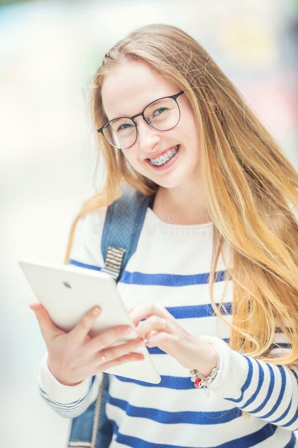 Portret van een glimlachende mooie tiener met tandsteunen Jong schoolmeisje met schooltas en tabletapparaat royalty-vrije stock fotografie