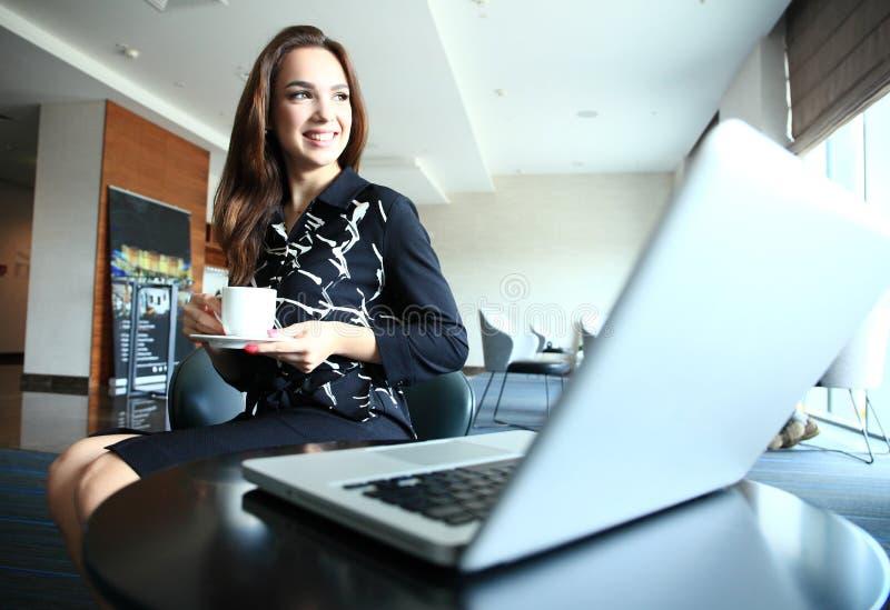 Portret van een glimlachende onderneemster die in bureau werken stock afbeeldingen