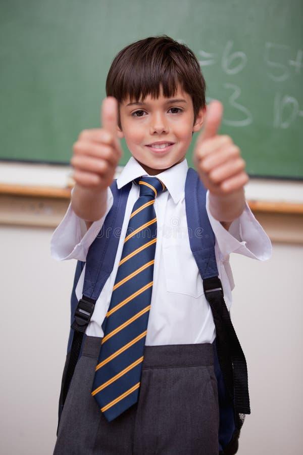 Portret van een glimlachende schooljongen met de omhoog duimen stock foto