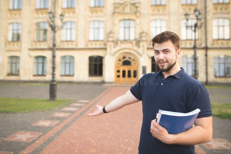 Portret van een glimlachende student met boeken en notitieboekjes in zijn handen die zich bij de ingang aan de universiteit bevin stock afbeelding