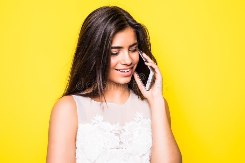 Portret van een glimlachende vrouw die op de telefoon over gele achtergrond spreken royalty-vrije stock afbeelding