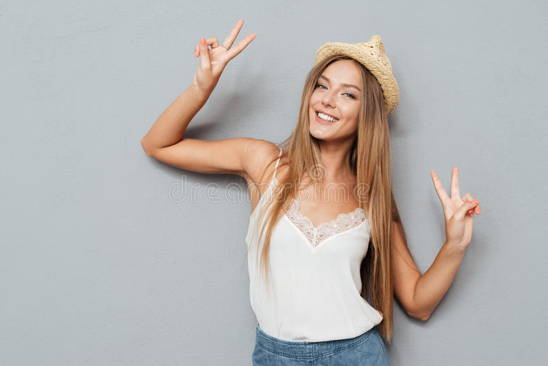 Portret van een glimlachende vrouw in hoed die vredesteken tonen stock afbeelding