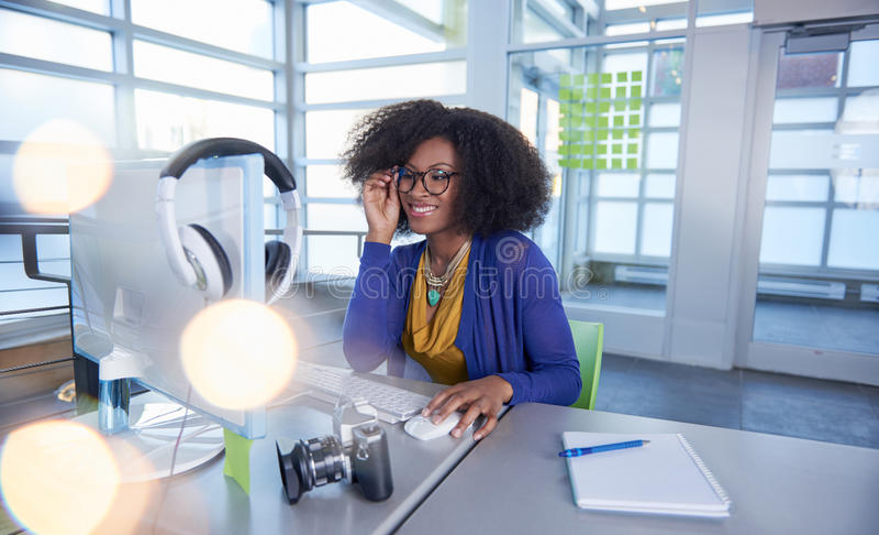 Portret van een glimlachende vrouw met een afro bij de computer in helder glasbureau royalty-vrije stock afbeelding