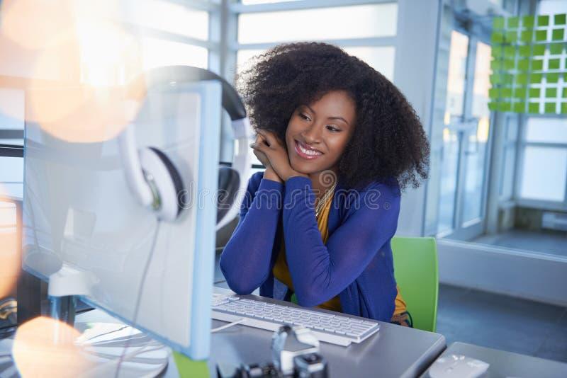 Portret van een glimlachende vrouw met een afro bij de computer in helder glasbureau stock fotografie