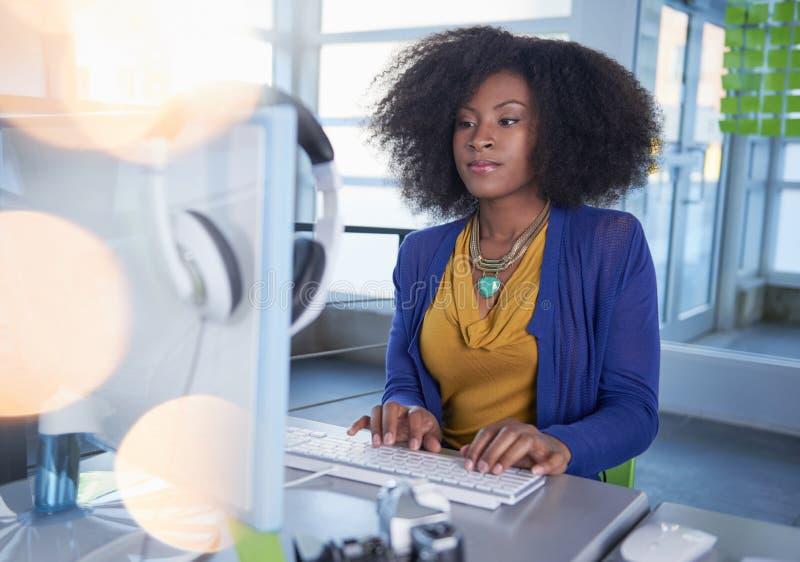 Portret van een glimlachende vrouw met een afro bij de computer in helder glasbureau royalty-vrije stock foto's