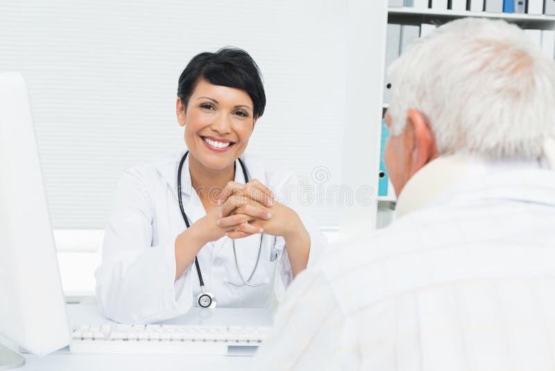 Portret van een glimlachende vrouwelijke arts met hogere patiënt stock fotografie