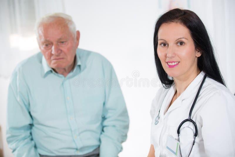 Portret van een glimlachende vrouwelijke arts met hogere patiënt op het medische kantoor royalty-vrije stock afbeelding