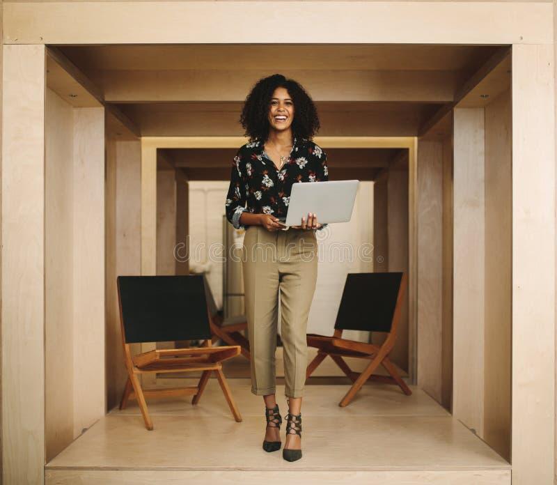 Portret van een glimlachende vrouwenondernemer die zich in bureaugreep bevinden royalty-vrije stock fotografie