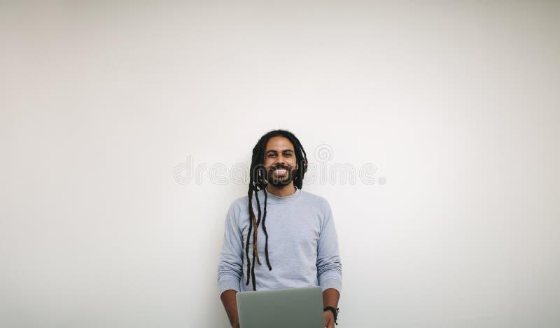 Portret van een glimlachende zakenman laptop houden die zich bevindt in o stock foto's