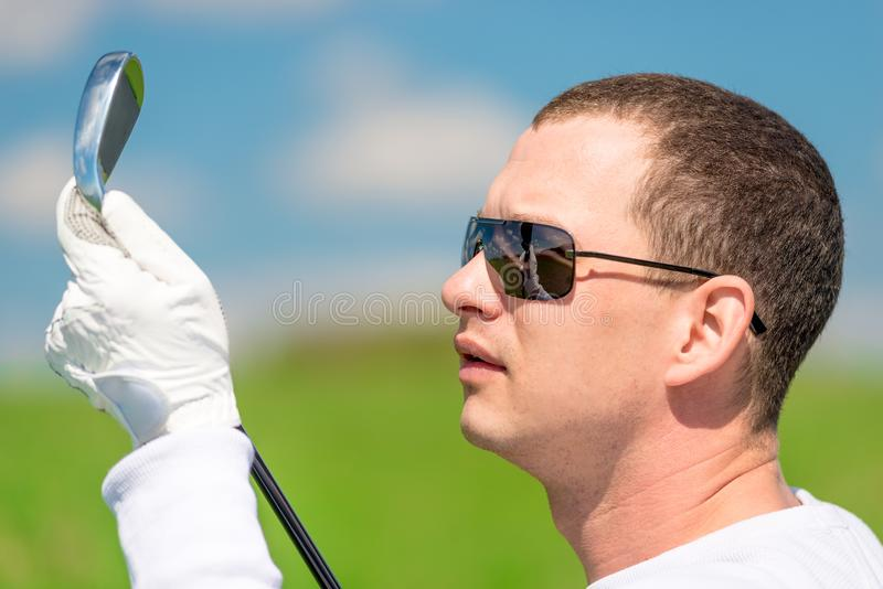 portret van een golfspeler die zijn golfclub bekijken stock afbeeldingen