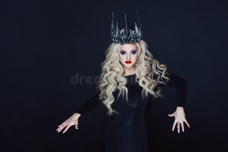 Portret van een Gotische Prinses Mooie jonge blondevrouw in metaalkroon en zwarte mantel royalty-vrije stock foto's
