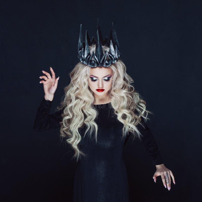 Portret van een Gotische Prinses Mooie jonge blondevrouw in metaalkroon en zwarte mantel stock foto