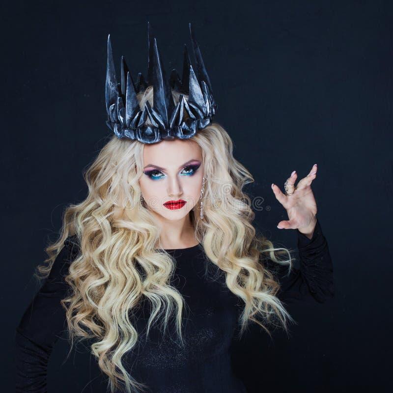 Portret van een Gotische Prinses Mooie jonge blondevrouw in metaalkroon en zwarte mantel stock fotografie