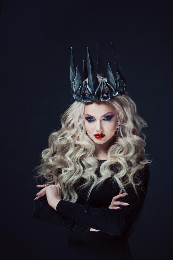 Portret van een Gotische Prinses Mooie jonge blondevrouw in metaalkroon en zwarte mantel royalty-vrije stock foto