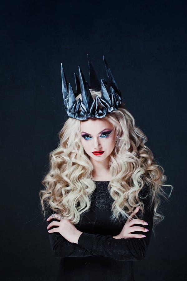 Portret van een Gotische Prinses Mooie jonge blondevrouw in metaalkroon en zwarte mantel royalty-vrije stock afbeelding