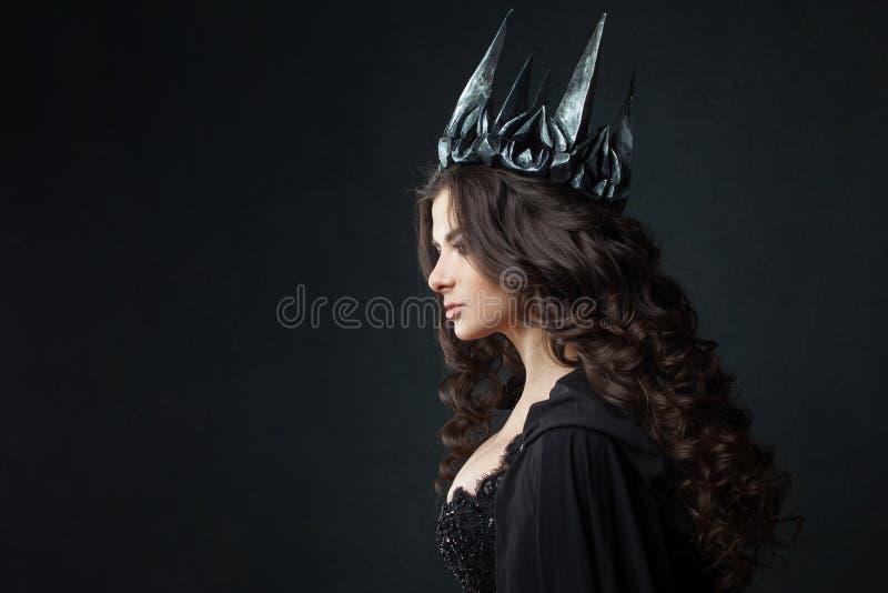 Portret van een Gotische Prinses Mooie jonge donkerbruine vrouw in metaalkroon en zwarte mantel stock foto's