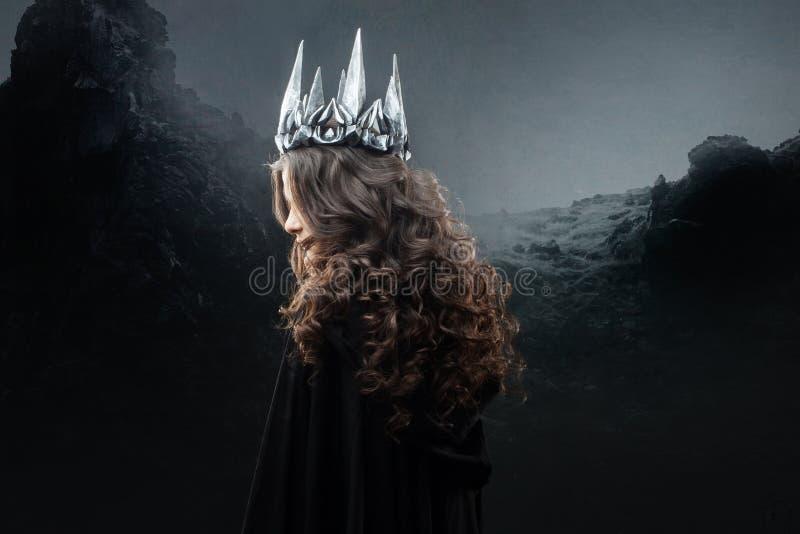 Portret van een Gotische Prinses Mooie jonge donkerbruine vrouw in metaalkroon en zwarte mantel royalty-vrije stock foto's