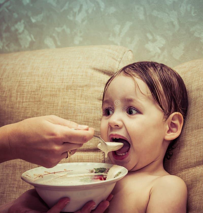 Portret van een grappig babymeisje dat een heerlijke nuttige oatmea eet royalty-vrije stock afbeeldingen
