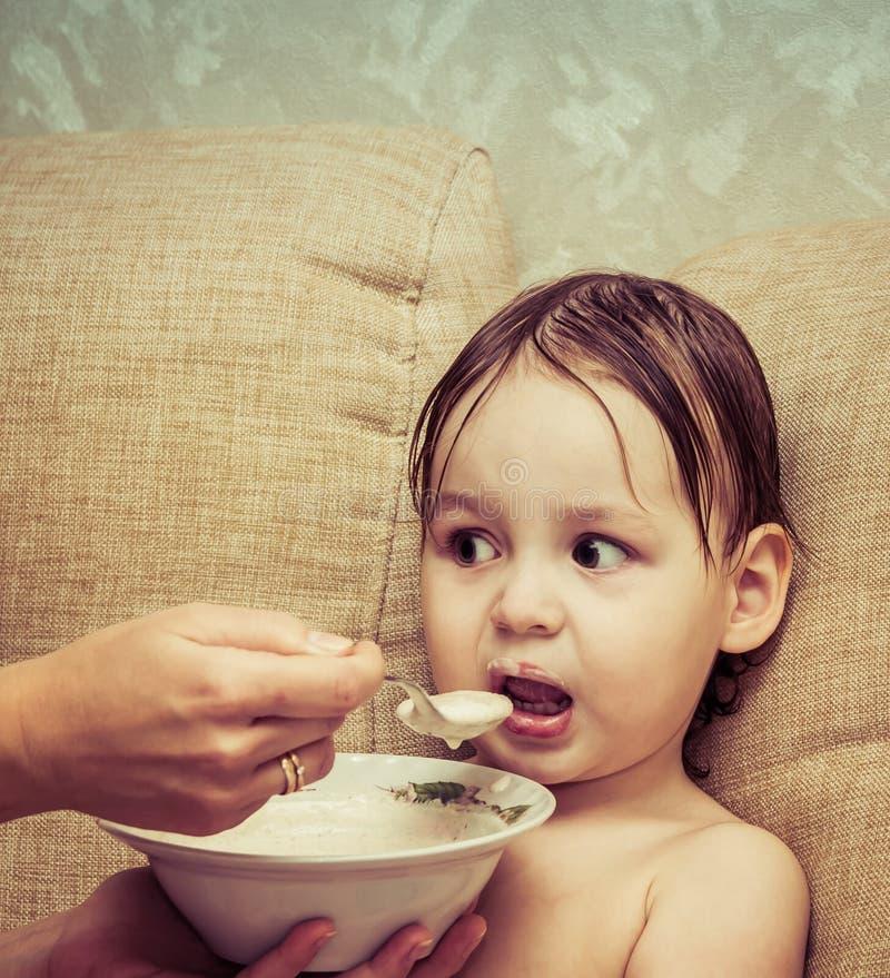 Portret van een grappig babymeisje dat een heerlijke nuttige oatmea eet stock afbeeldingen