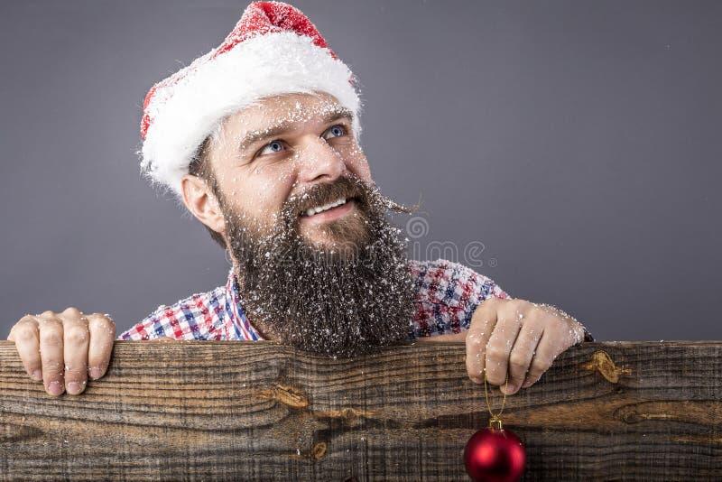 Portret van een grappige gebaarde mens die met santa GLB een rode rou houden royalty-vrije stock fotografie